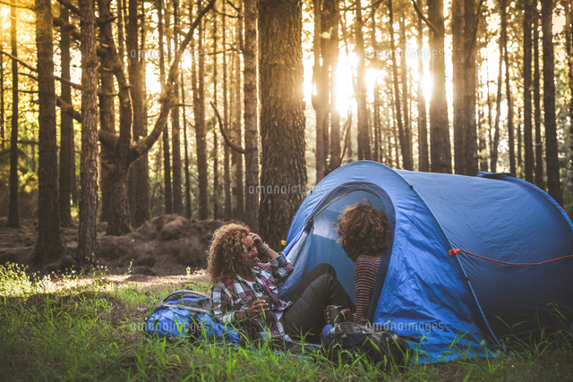 Two Women Sitting In Tent At Forest