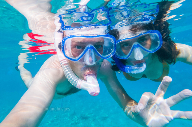 Couple Using Snorkels While Swimming Undersea
