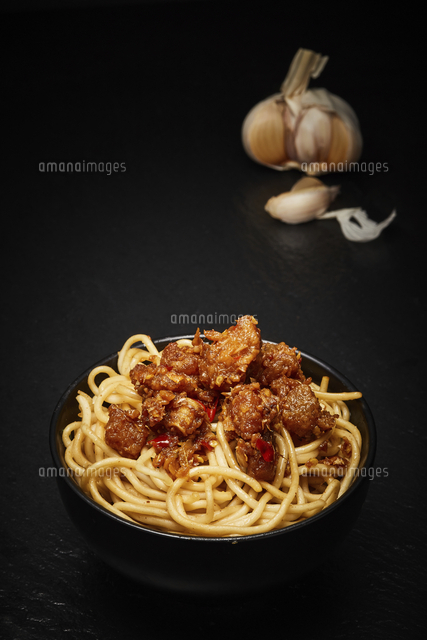 Spicy fish and rice noodles on a dark background