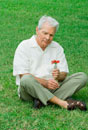 man sitting on grass, holding flower