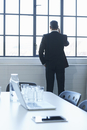 Rear view of business man chatting on smartphone in conference room