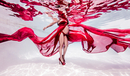 Underwater view of pregnant woman draped in sheer red fabric