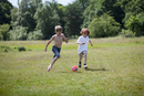 Children playing soccer in grassy field