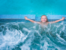 Overhead portrait of cute boy splashing in outdoor swimming pool