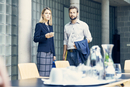 Businesswoman and man standing by boardroom table