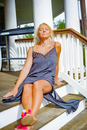 Mid adult woman in sundress reclining on porch stairs sunbathing
