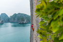 Man rock climbing on limestone rock, Ha Long Bay, Vietnam