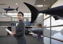 Mixed race businesswoman watching shark in office