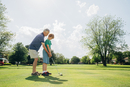 Caucasian grandfather teaching grandson golf on course