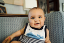 Portrait of smiling Mixed Race baby boy on chair