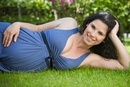 Portrait of pregnant woman lying on lawn
