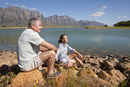 Senior couple sitting on rocks by lake