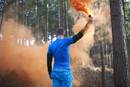 A man lets off a flare in the woods