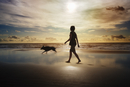 Silhouette of woman and dog walking on beach
