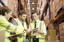 Businessman and workers talking in warehouse