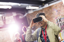 Man trying virtual reality simulator glasses at technology conference