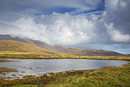 Tranquil view clouds and rainbow over rolling hills beyond lake, Loch Aineort, South Uist, Outer Hebrides