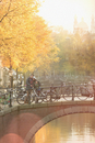 Portrait couple with bicycles hugging on urban autumn bridge over canal, Amsterdam