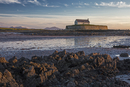 Tranquil medieval island church at low tide, St Cwyfans Church, Anglesey, Wales
