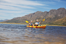 Active senior couple kayaking on sunny summer lake
