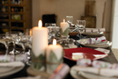 Candles, placesettings and Christmas crackers on table