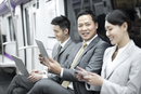 Business persons using digital products in subway train