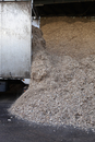 Stored organic waste heaped up in a large warehouse for biomass fuel 有oduction.