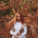 Woman with long red hair standing in an autumn forest, holding a small branch.