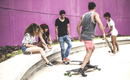 A group of young skateboarders in a skate park.
