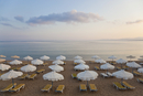 High angle view of rows of sun loungers and umbrellas on a sandy beach in the Mediterranean.