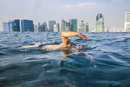 Man swimming in infinity pool on roof terrace, cityscape with skyscrapers in the distance.