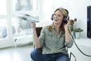 Woman holding record hearing music with headphones
