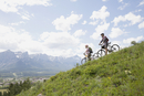 Couple standing with mountain bikes on hillside