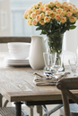 Rose bouquet and dinnerware wooden dining table