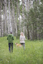 middle-aged couple walking their dog in the woods