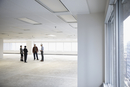 Contractor and architects talking in unfinished, empty open plan office