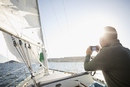 Man using camera on sunny sailboat