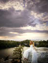 Portrait of Bride on rocks overlooking lake at sunset