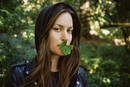 Portrait of woman with clover leaves in mouth in forest