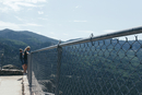 Siblings looking at mountains while standing on chainlink fence against sky