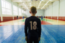 Rear view of player standing at indoor soccer court