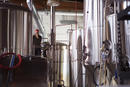 Brewer standing by storage tanks at brewery
