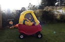 Girl driving toy car on grassy field in backyard