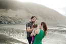 Family enjoying with daughter at beach by mountain