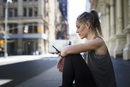 Athlete using mobile phone while sitting at sidewalk in city