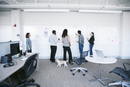 Business people writing notes on whiteboard white discussing in office