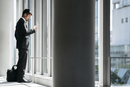 Side view of businessman using smart phone while standing by window in office