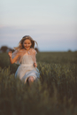 Cheerful girl running on grassy field against sky during sunset