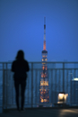 Silhouette woman standing at observation point against illuminated Tokyo Tower at dusk
