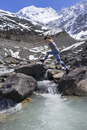 Side view of woman jumping on rocks by river against snowcapped mountains